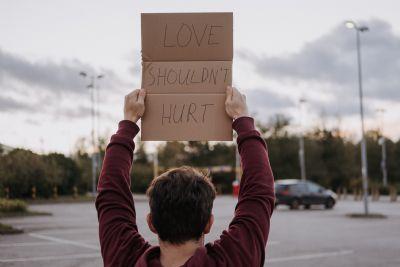 Jongen met bord: Love shouldn't hurt